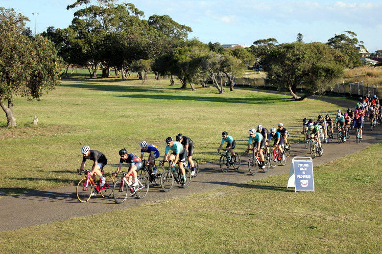 Group of bicycle riders racing in a group at Heffron Park in a line