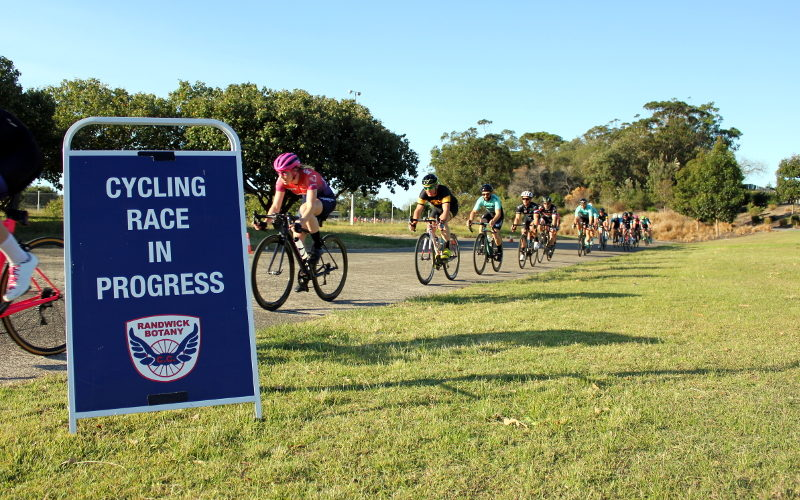 """Sign reads """"Cycling Race in Progress"""" with racers going past behind it"""