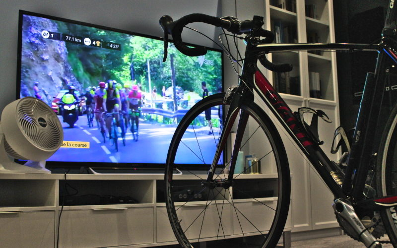 Cycling in AEST: Giant bicycle on indoor trainer in front of Tour de France on television with fan