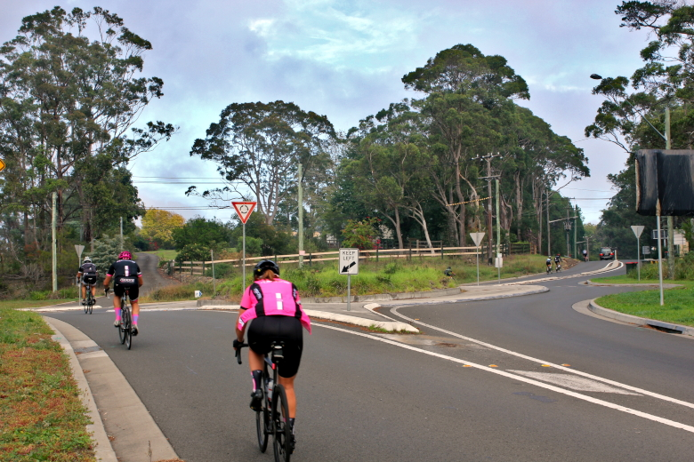 Cyclists ascending through roundabout while cycling Galston Gorge West.