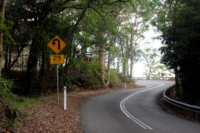 Road on Bobbin Head West with left hairpin road sign approaching building