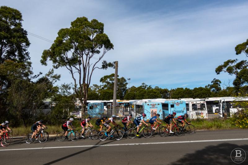 Cyclists racing past bus depot at Beaumont Road, Mount Kuring-gai.