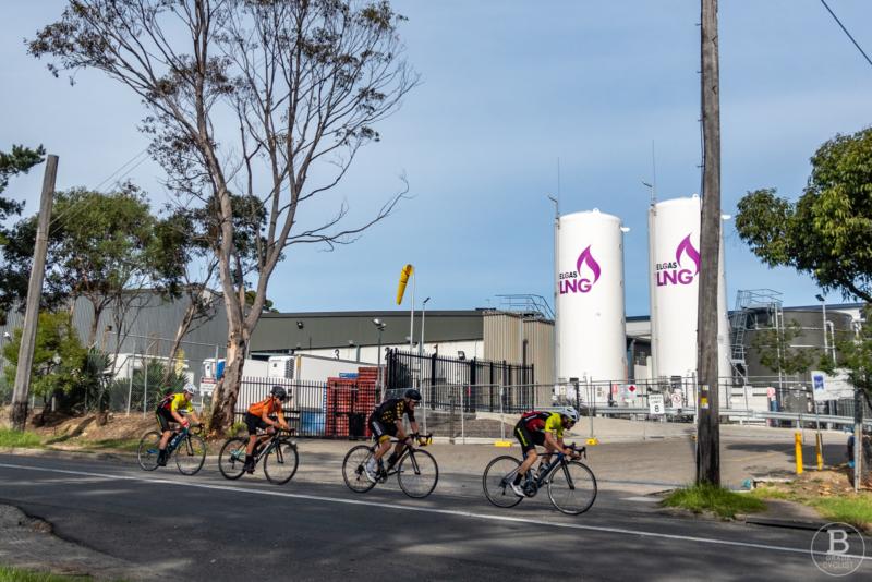 Riders racing past a factory at Beaumont Road, Mount Kuring-gai.